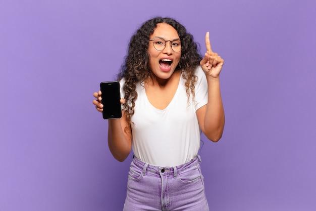 Jonge spaanse vrouw die zich als een gelukkig en opgewonden genie voelt na het realiseren van een idee, opgewekt de vinger opstekend, eureka !. slimme telefoon concept