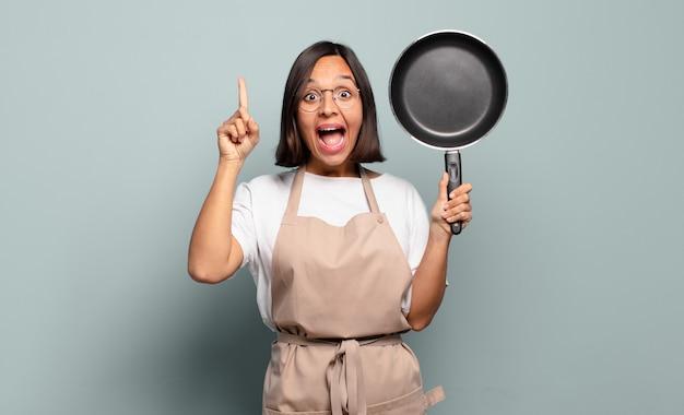 Jonge spaanse vrouw die zich als een gelukkig en opgewonden genie voelt na het realiseren van een idee, opgewekt de vinger opstekend, eureka!