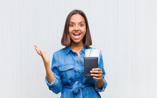 Jonge spaanse vrouw die zich blij, opgewonden, verrast of geschokt voelt, glimlacht en verbaasd is over iets ongelooflijks