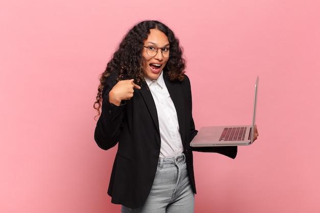 Jonge spaanse vrouw die zich blij, verrast en trots voelt en naar zichzelf wijst met een opgewonden, verbaasde blik. laptop concept