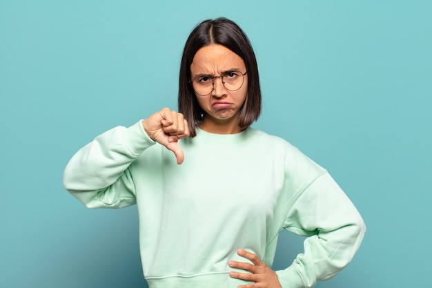 Jonge spaanse vrouw die zich boos, boos, geïrriteerd, teleurgesteld of ontevreden voelt, duimen naar beneden laat zien met een serieuze blik