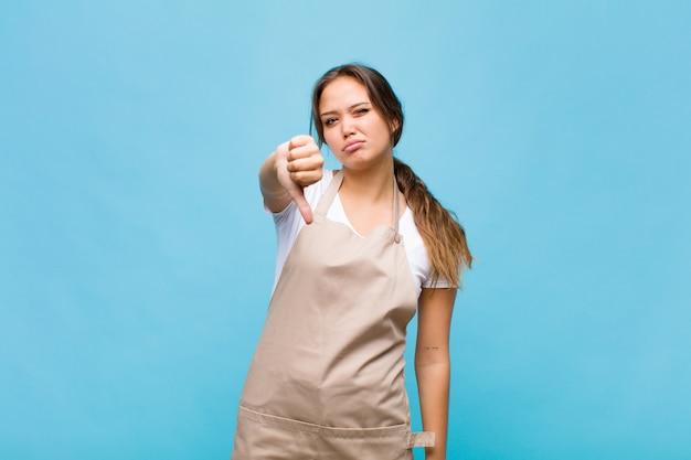 Jonge spaanse vrouw die zich boos, boos, geïrriteerd, teleurgesteld of ontevreden voelt, duimen naar beneden toont met een serieuze blik