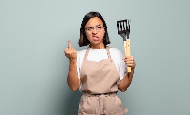 Jonge spaanse vrouw die zich boos, geïrriteerd, opstandig en agressief voelt, de middelvinger omdraait, terugvecht