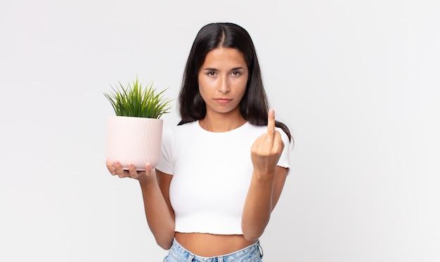 Jonge spaanse vrouw die zich boos, geïrriteerd, opstandig en agressief voelt en een decoratieve kamerplant vasthoudt