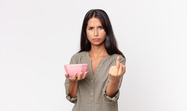 Jonge spaanse vrouw die zich boos, geïrriteerd, opstandig en agressief voelt en een lege kom of pot vasthoudt