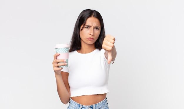 Jonge spaanse vrouw die zich boos voelt, duimen naar beneden laat zien en een afhaalkoffiecontainer vasthoudt