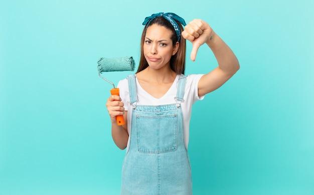 Jonge spaanse vrouw die zich boos voelt, duimen naar beneden laat zien en een muur schildert