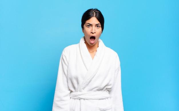 Jonge spaanse vrouw die zich doodsbang en geschokt voelde, met mond wijd open van verbazing. badjas concept