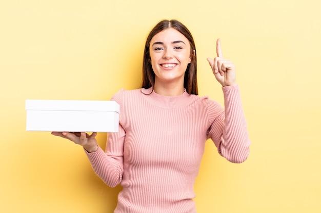 Jonge spaanse vrouw die zich een gelukkig en opgewonden genie voelt na het realiseren van een idee. lege doos concept