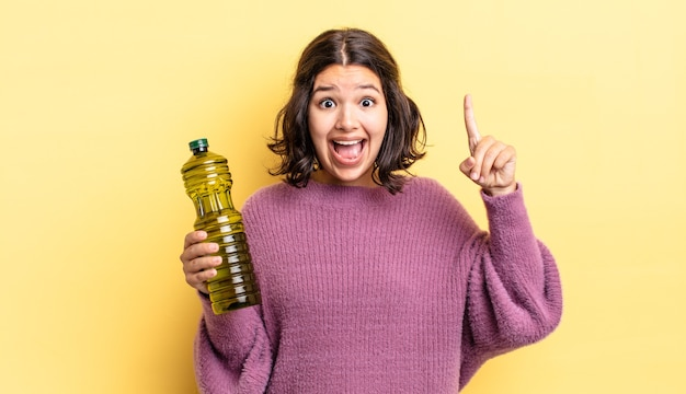 Jonge spaanse vrouw die zich een gelukkig en opgewonden genie voelt na het realiseren van een idee. olijfolie concept