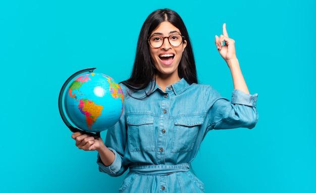 Jonge spaanse vrouw die zich een gelukkig en opgewonden genie voelt na het realiseren van een idee, vrolijk de vinger opstekend, eureka!. aarde planeet concept