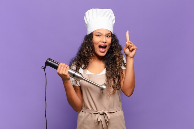 Jonge spaanse vrouw die zich een gelukkig en opgewonden genie voelt na het realiseren van een idee, vrolijk de vinger opstekend, eureka!. chef-kok concept