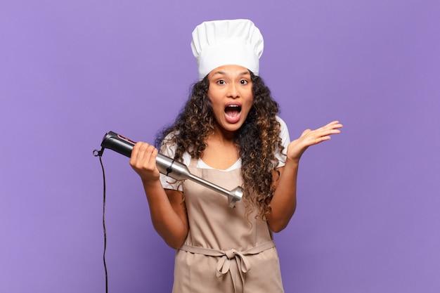 Jonge spaanse vrouw die zich extreem geschokt en verrast, angstig en in paniek voelt, met een gestreste en met afschuw vervulde blik. chef-kok concept