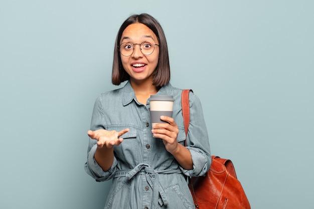 Jonge spaanse vrouw die zich extreem geschokt en verrast, angstig en in paniek voelt, met een gestreste en met afschuw vervulde blik