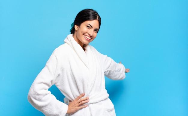 Jonge spaanse vrouw die zich gelukkig en opgewekt voelt, je lacht en verwelkomt, je uitnodigt met een vriendelijk gebaar. badjas concept