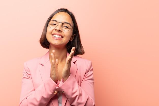 Jonge spaanse vrouw die zich gelukkig en succesvol voelt, lacht en in de handen klapt