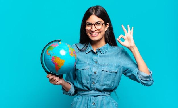 Jonge spaanse vrouw die zich gelukkig, ontspannen en tevreden voelt, goedkeuring toont met een goed gebaar, glimlachend. aarde planeet concept