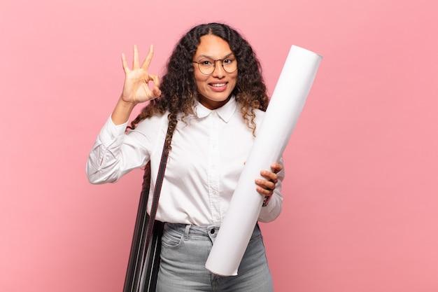 Jonge spaanse vrouw die zich gelukkig, ontspannen en tevreden voelt, goedkeuring toont met een goed gebaar, glimlachend. architect concept