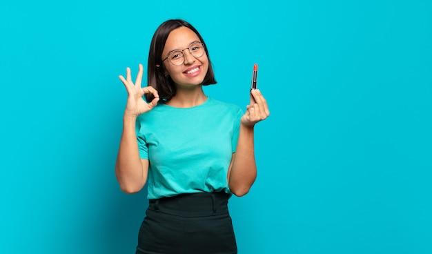 Jonge spaanse vrouw die zich gelukkig, ontspannen en tevreden voelt, goedkeuring toont met een goed gebaar, glimlachend