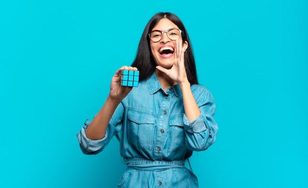 Jonge spaanse vrouw die zich gelukkig, opgewonden en positief voelt, een grote schreeuw geeft met de handen naast de mond, roept. intelligentie probleem concept