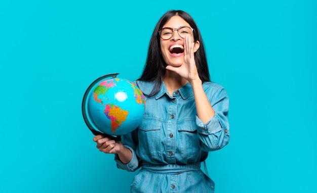 Jonge spaanse vrouw die zich gelukkig, opgewonden en positief voelt, een grote schreeuw geeft met de handen naast de mond, roept