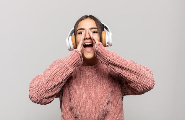 Jonge spaanse vrouw die zich gelukkig, opgewonden en positief voelt, een grote schreeuw geeft met de handen naast de mond, roept,