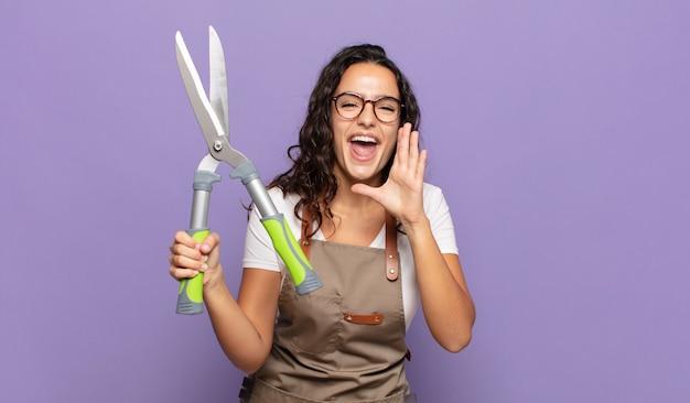 Jonge spaanse vrouw die zich gelukkig, opgewonden en positief voelt, een grote schreeuw geeft met handen naast de mond, roept