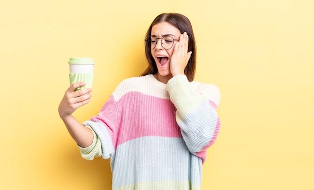 Jonge spaanse vrouw die zich gelukkig, opgewonden en verrast voelt. afhaal koffie concept