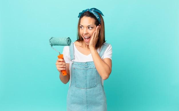 Jonge spaanse vrouw die zich gelukkig, opgewonden en verrast voelt en een muur schildert