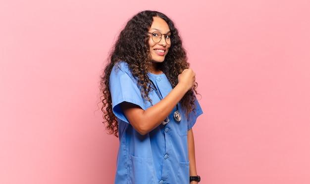 Jonge spaanse vrouw die zich gelukkig, positief en succesvol voelt, gemotiveerd wanneer ze voor een uitdaging staat of goede resultaten viert. verpleegkundige concept