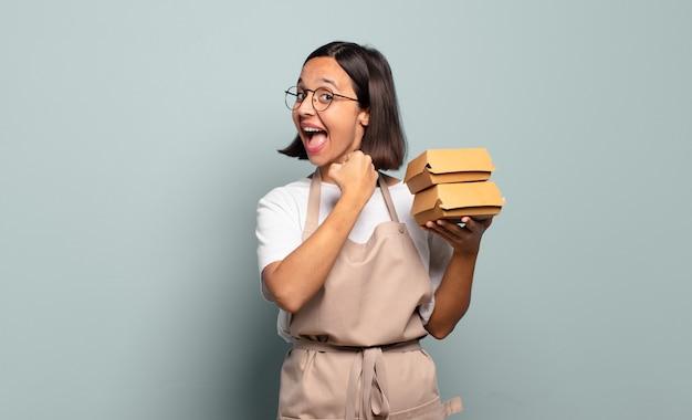 Jonge spaanse vrouw die zich gelukkig, positief en succesvol voelt, gemotiveerd wanneer ze voor een uitdaging staat of goede resultaten viert