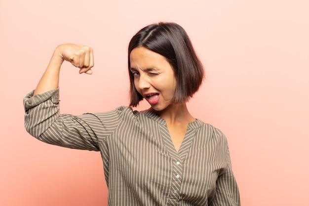 Jonge spaanse vrouw die zich gelukkig, tevreden en krachtig voelt, buigzaam fit en gespierde biceps, die er sterk uitziet na de sportschool