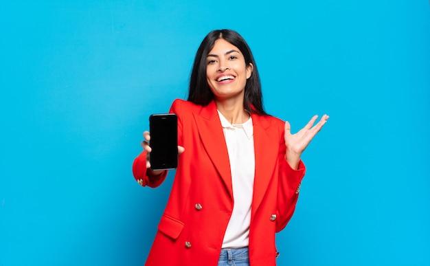 Jonge spaanse vrouw die zich gelukkig, verrast en opgewekt voelt, glimlachend met een positieve houding, een oplossing of idee realiserend. telefoon scherm kopie ruimte