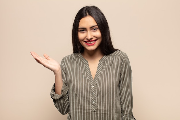 Jonge spaanse vrouw die zich gelukkig, verrast en opgewekt voelt, glimlachend met een positieve houding, een oplossing of idee realiserend