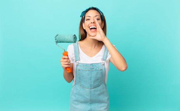 Jonge spaanse vrouw die zich gelukkig voelt, een grote schreeuw geeft met de handen naast de mond en een muur schildert