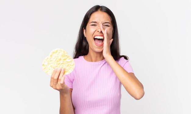 Jonge spaanse vrouw die zich gelukkig voelt, een grote schreeuw geeft met de handen naast de mond en een rijstkoekje vasthoudt. dieet concept