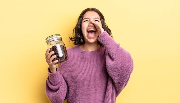 Jonge spaanse vrouw die zich gelukkig voelt, een grote schreeuw geeft met de handen naast de mond. koffiebonen concept