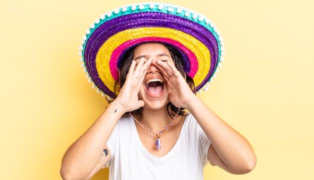 Jonge spaanse vrouw die zich gelukkig voelt, een grote schreeuw geeft met de handen naast de mond. mexicaanse hoed concept