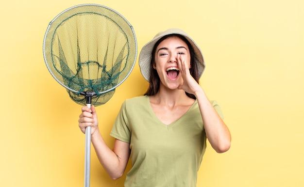 Jonge spaanse vrouw die zich gelukkig voelt, een grote schreeuw geeft met de handen naast het visnetconcept van de mond