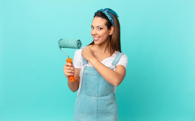 Jonge spaanse vrouw die zich gelukkig voelt en een uitdaging aangaat of een muur viert en schildert