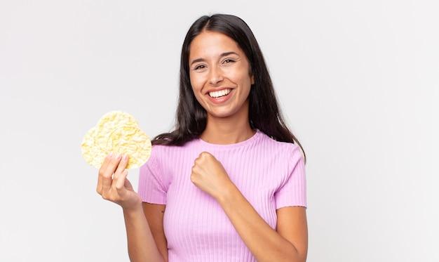 Jonge spaanse vrouw die zich gelukkig voelt en een uitdaging aangaat of een rijstkoekje viert en vasthoudt. dieet concept