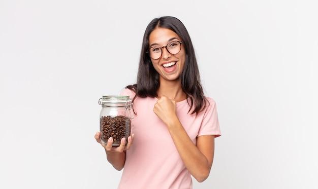 Jonge spaanse vrouw die zich gelukkig voelt en een uitdaging aangaat of viert en een fles koffiebonen vasthoudt