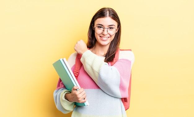 Jonge spaanse vrouw die zich gelukkig voelt en een uitdaging aangaat of viert. studentenconcept