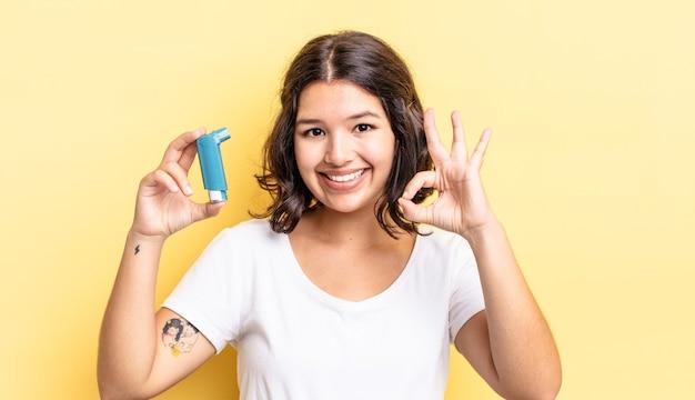 Jonge spaanse vrouw die zich gelukkig voelt, goedkeuring toont met een goed gebaar. astma concept