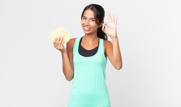 Jonge spaanse vrouw die zich gelukkig voelt, goedkeuring toont met een goed gebaar. fitness dieet concept