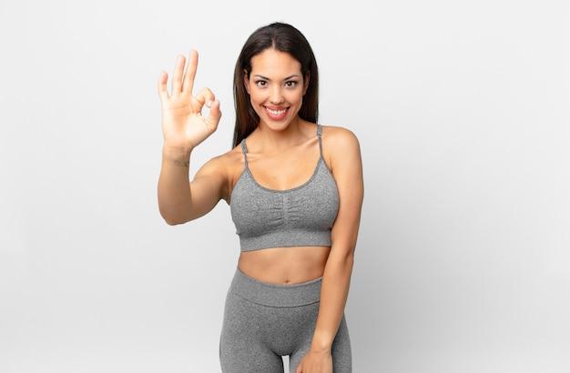 Jonge spaanse vrouw die zich gelukkig voelt, goedkeuring toont met een goed gebaar. fitnessconcept