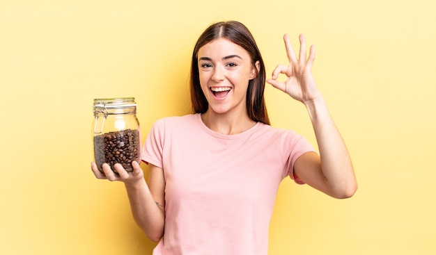 Jonge spaanse vrouw die zich gelukkig voelt, goedkeuring toont met een goed gebaar. koffiebonen concept