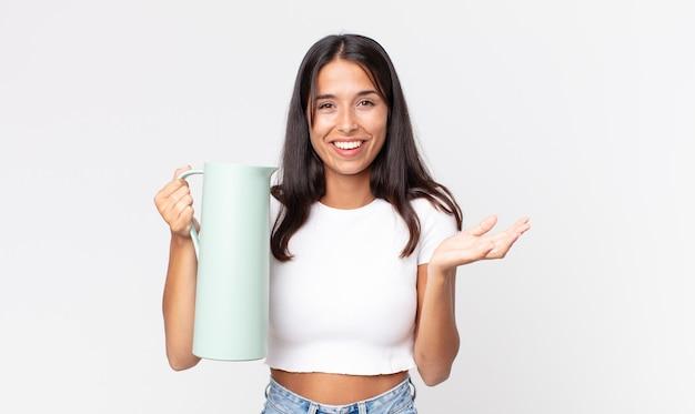 Jonge spaanse vrouw die zich gelukkig voelt, verrast een oplossing of idee realiseert en een koffiethermoskan vasthoudt