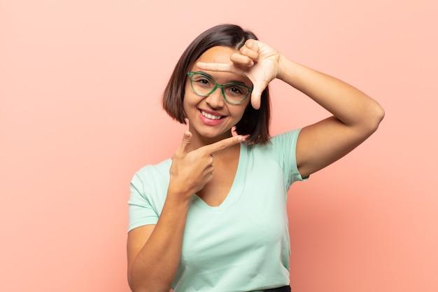 Jonge spaanse vrouw die zich gelukkig, vriendelijk en positief voelt, lacht en een portret of fotolijst met handen maakt