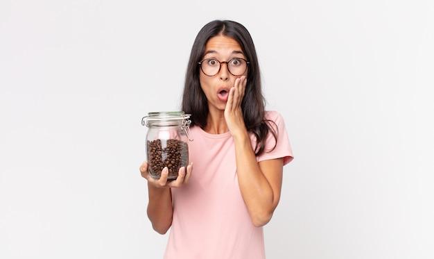Jonge spaanse vrouw die zich geschokt en bang voelt en een fles koffiebonen vasthoudt